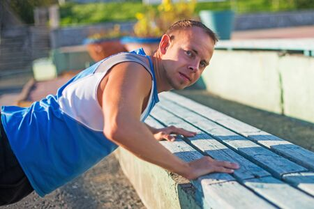 pushed: Athletic man trains, pushed from the bench on stadium. concept of health and strength