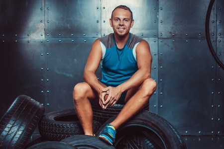 crossfit: Sportsman sitting on the tire machine. Concept of CrossFit, health and strength Stock Photo