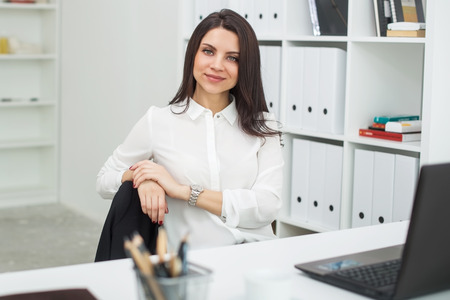Young business woman with notebook in the office, workplace. Stock Photo