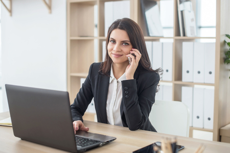 Business woman with notebook in office, workplace, talking on phone.