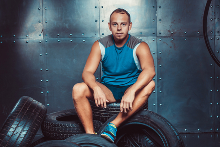 sportsmen: Sportsmen. fit male trainer man keeps the car tires, concept  fitness workout strenght power Stock Photo