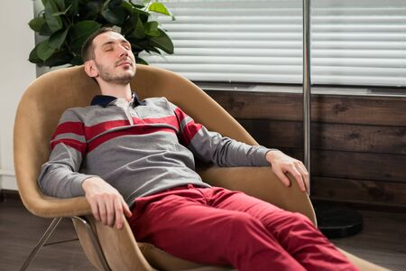 The young man relaxes, lies in a chair with his eyes closed. Standard-Bild