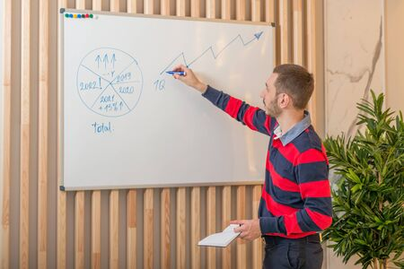Businessman standing by the blackboard and draws a growth graph. Concept for successful business. Standard-Bild