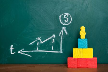 Toy Man stands on top of a pedestal near a blackboard on which a graph is drawn. Standard-Bild