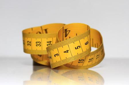 millimetre: yellow measuring tape is lying on a shiny Stock Photo