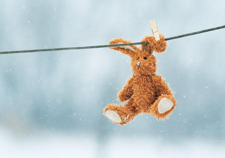sad little toy rabbit hanging from a rope in the snow Stock Photo