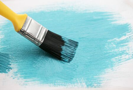 art brush puts a bright blue brush strokes on the surface of the  tree