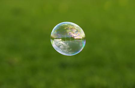 Bunte Seifenblase mit Reflexion der Landschaft und der Himmel fliegen auf einer hellen Sommerwiese an einem sonnigen Tag Lizenzfreie Bilder