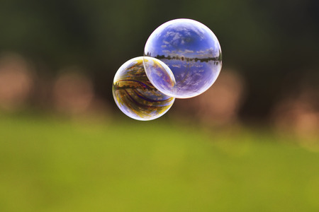 two bright bubble with shiny reflections on the background of green meadows  Stockfoto