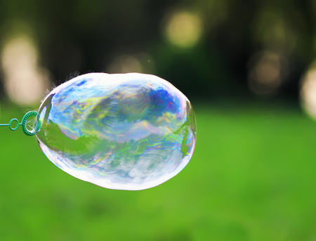 iridescent soap bubble is inflated and bursts leaving a spray
