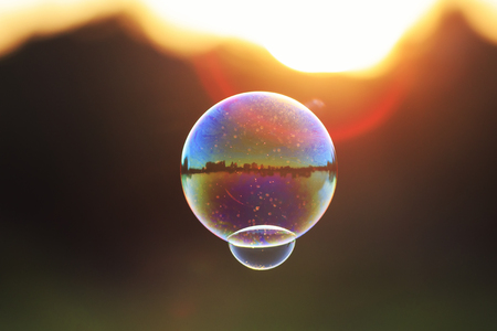 iridescent soap bubble with reflection landscape flies to sunset over summer meadow