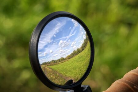 rural landscape with sky and field is reflected in the mirror of the bike Stockfoto
