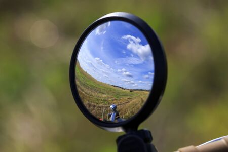 rural landscape with blue sky and field is reflected in the mirror of the bike