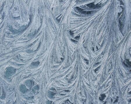 beautiful holiday background of intricate frosty pattern on glass