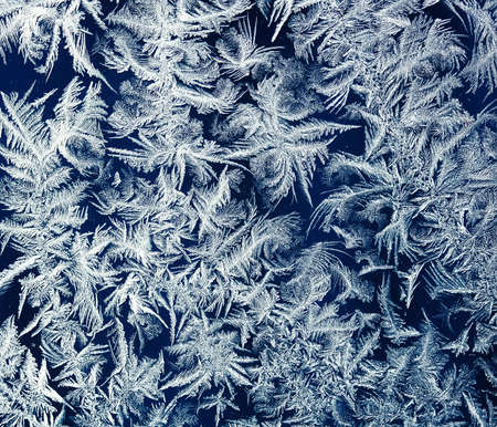holiday background from a shiny frosty pattern on intricate blue glass