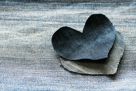 background of denim for the background and two hearts of blue fabric Lizenzfreie Bilder