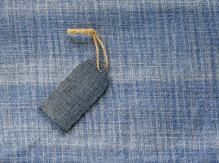 blank price tag on a rope on the background of denim for a seasonal sales Lizenzfreie Bilder