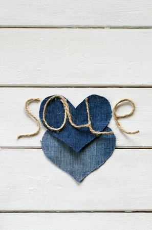 original background with a stylish inscription from sale of twine in my hand and hearts denim Lizenzfreie Bilder