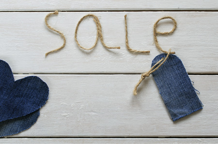 original background with a stylish inscription from sale of twine in my hand, a blank price tag and hearts of denim Lizenzfreie Bilder