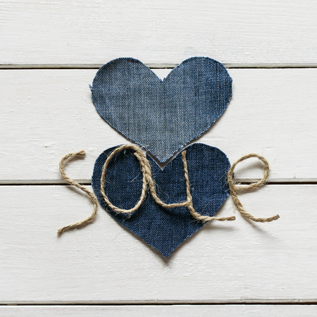 original background with a stylish inscription from sale of twine in my hand and a pair of hearts from denim fabric on a white tree