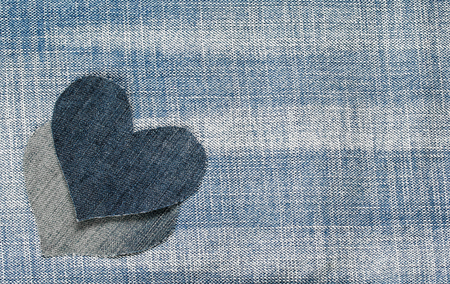 background of the two denim hearts lie on trendy textured blue fabric