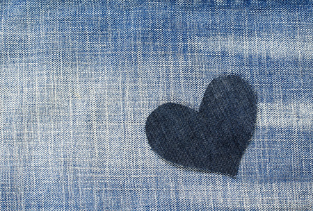 one stylish heart cut from blue denim in a trendy background