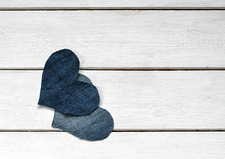two stylish hearts are cut from blue denim lying together on white wooden background