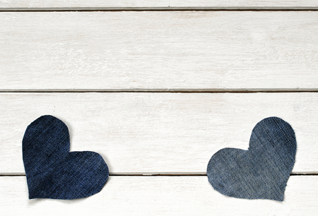 two stylish hearts are cut from blue denim fabric lying on a white wooden background
