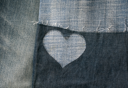 -background of different stripes of denim fabrics and holes in the heart Lizenzfreie Bilder