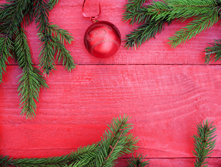 festive background of fragrant green fir tree branches with shiny bows and Christmas ball on a red wooden table