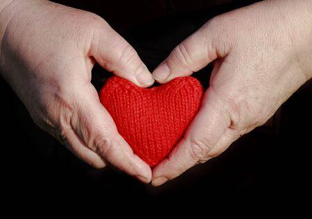 handen van een bejaarde vrouwelijke gepensioneerde bedrijf zorgvuldig gebreide rood hart