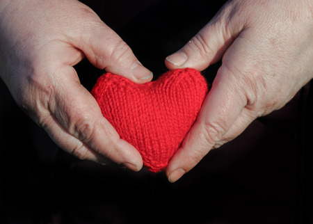 old man with wrinkled hands with fingers knitted red heart