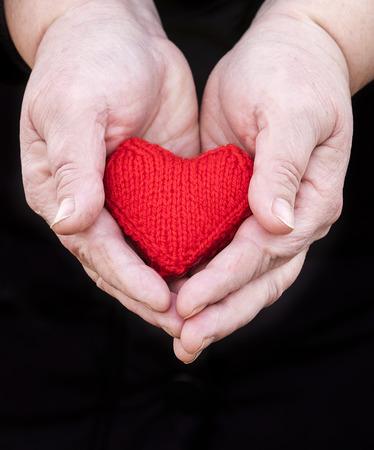 paar handen van oudere man met gerimpelde handen zachtjes houden gebreide rood hart op een zwarte achtergrond