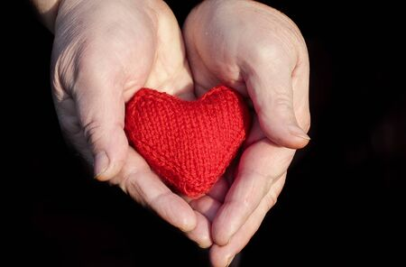 hands of an elderly pensioner with wrinkled hands gently holding knitted red heart on a black background Stockfoto