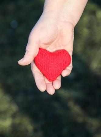 de hand van de vrouw houdt een rood gebreid hart naar voren