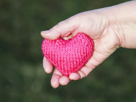 old man holds in the palm of your hand knitted pink heart extending forward Stockfoto