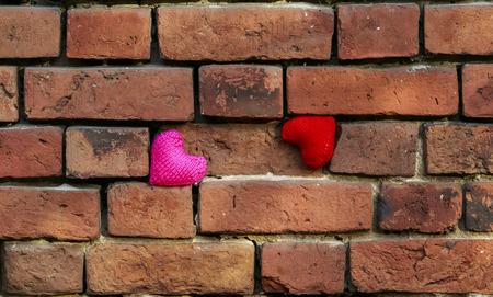 twee gebreide harten rood en roze staan ??op een afbrokkelende oude rode bakstenen getextureerde muur is metselwerk