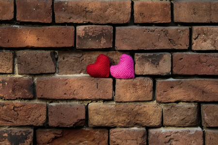 two knit hearts red and pink are standing on a crumbling old red brick textured wall is masonry Stockfoto