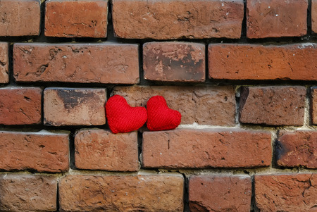 two knitted red heart on a crumbling old red brick textured wall is masonry