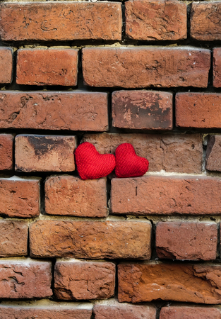 two knitted red heart on a crumbling old red brick textured wall vertically Stockfoto