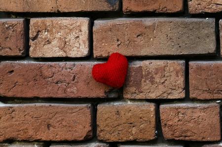 een gebreide rode hart opknoping op oude bouwvallige getextureerde rode bakstenen muur buiten