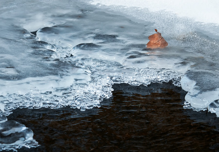 natural background in the late autumn water freezes and is covered with a thick cold ice Stockfoto