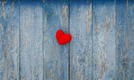 schattig rood hart gebreid van garen op de muur met oude peeling blauwe verf