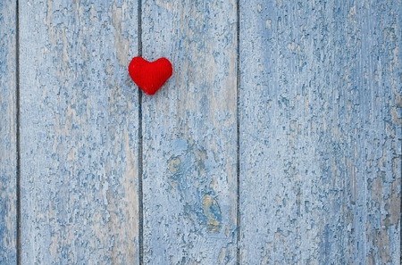 bright red heart made of yarn against the wall of wood with a shabby country blue paint Stockfoto