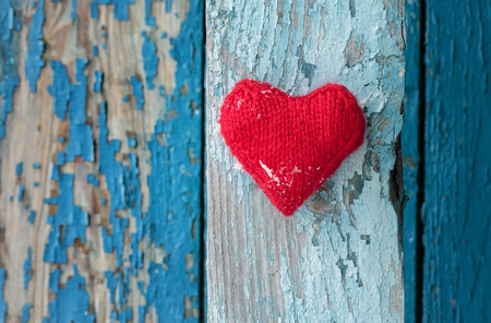 bright red heart made of yarn against the wall of wood with a shabby country blue paint different shades of stripes
