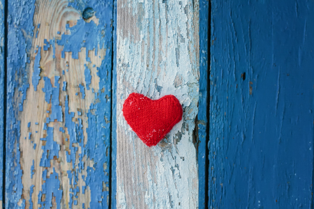 red heart made of yarn against the wall of wood with a shabby country blue paint different shades of stripes