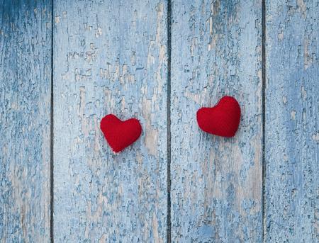 twee helder rood hart gemaakt van garen op een achtergrond van houten wanden met een shabby oude blauwe verf strepen