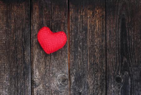 helder liefdesnoepje hart van garen op de achtergrond van de houten wanden van oude donkere teerplanken