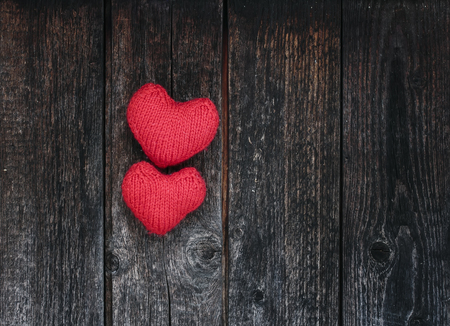 two bright red hearts made of yarn on a background of the wooden walls of old dark tar boards Stockfoto