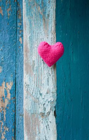 mooi roze hart gemaakt van garen op een achtergrond van een houten muur met blauwe schillen verf Stockfoto